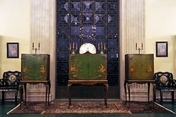 The cabinet containing the photograph of Bahá'u'lláh is to the left in the set. The other cabinets contain paintings of Bahá'u'lláh and the Báb. They are located in the Bahá'í International Archives.